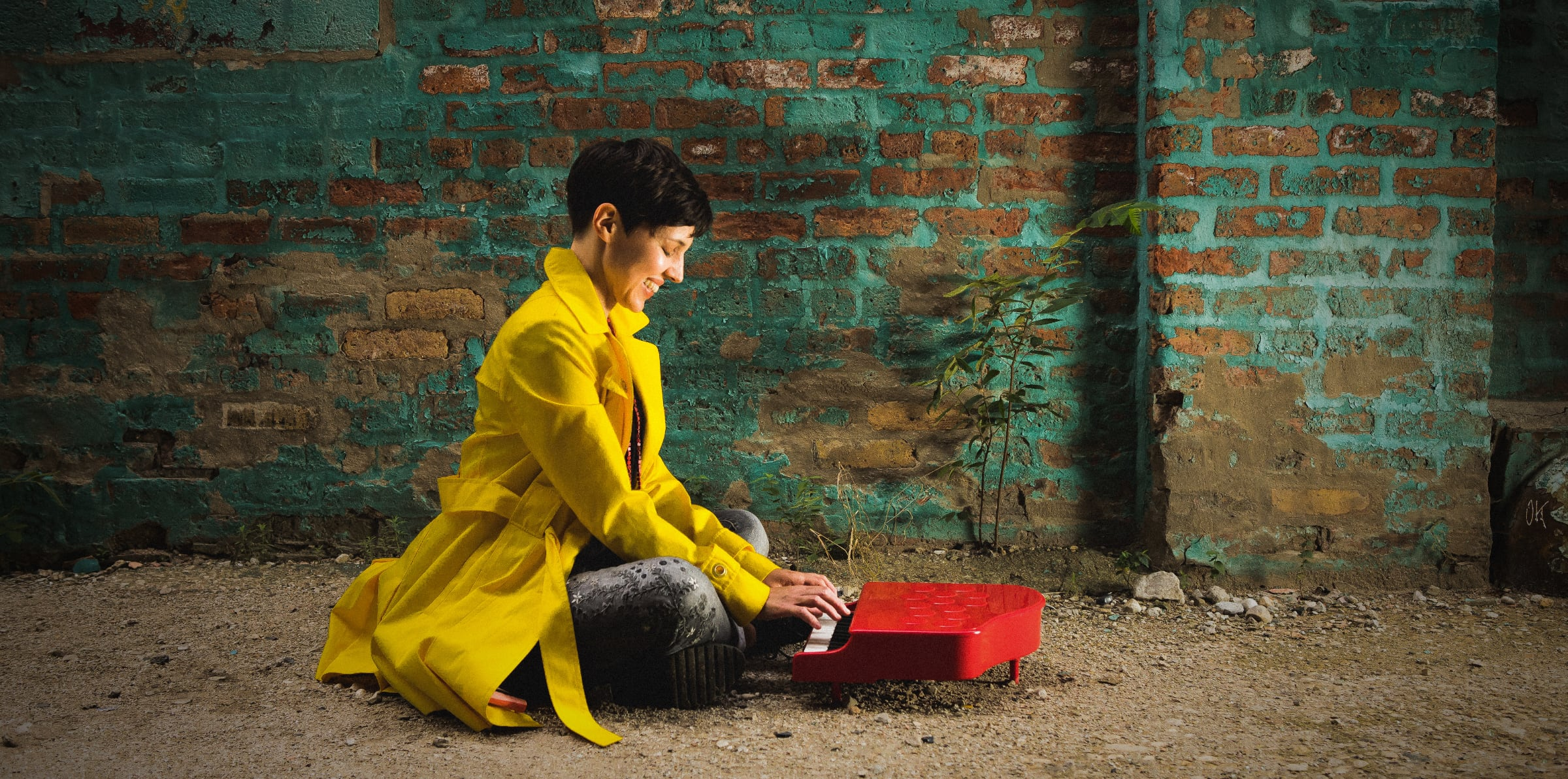 Diana Lawrence wearing a yellow coat, sitting at a red toy piano